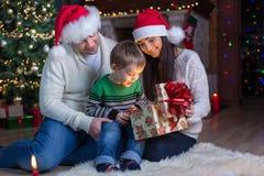 假日,礼物,圣诞节概念-有礼物盒的愉快的母亲、父亲和儿童男孩 图库摄影