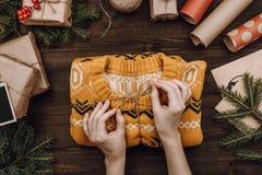 假日flatlay安排用包装被编织的毛线衣的妇女的手 库存照片