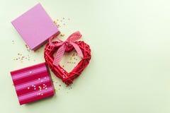 假日giftboxes和手工制造心脏在淡色黄色背景 图库摄影