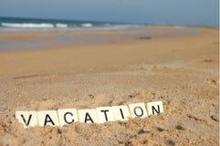 假期信件在一个晴朗的海滩的与海在背景中 免版税库存照片