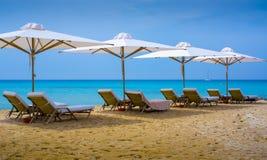 假期假日-四使躺椅靠岸在海滩的帐篷下地中海与在背景的一条游艇 免版税库存照片