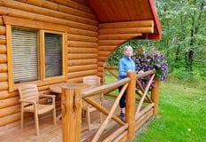 假期出租木客舱门廊的妇女  图库摄影