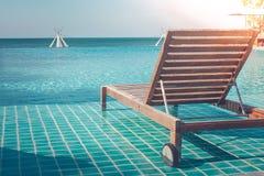 假期和假日概念:关闭在游泳池的木沙发床晒日光浴和休息的在季节性夏天的旅行 免版税库存照片