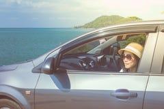 假期和假日概念:在海,画象妇女佩带的太阳镜和感觉的幸福的愉快的家用汽车旅行 库存照片