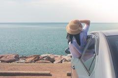 假期和假日概念:在海,画象妇女佩带的织法帽子和感觉的幸福的愉快的家用汽车旅行 库存照片