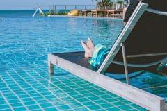 假期和假日概念:在游泳池旁边的沙发床的妇女在手段 图库摄影