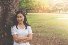 假期和假日概念:妇女佩带的白色T恤杉 她站立在绿草和感觉放松和幸福 图库摄影