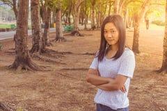 假期和假日概念:妇女佩带的白色T恤杉 她站立在绿草和感觉放松和幸福 库存图片