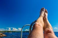 假期夏天视图-反对水和蓝天的腿 免版税库存照片
