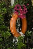 假期橙色lifebuoy在海的热带花背景  免版税库存照片