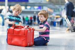 继续假期的两个兄弟男孩在机场绊倒 免版税库存照片