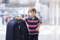 继续假期的小男孩绊倒带着手提箱在机场 免版税库存照片