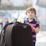 继续假期的小男孩绊倒带着手提箱在机场 库存图片