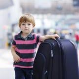 继续假期的小男孩绊倒带着手提箱在机场 免版税图库摄影