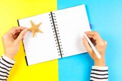 假期计划概念 妇女在开放旅行笔记本的手文字在蓝色和黄色背景 免版税图库摄影