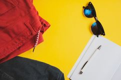 假期设备 红色短裤、牛仔布夹克、太阳镜和笔记本顶视图有笔的在黄色背景 免版税库存照片