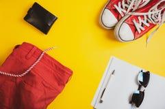 假期设备 红色短裤、皮革钱包、牛仔布夹克、太阳镜和笔记本顶视图有笔的在黄色背景 库存图片