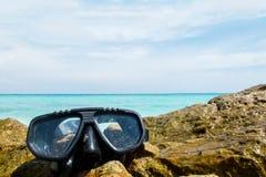 假期起动这里概念、佩戴水肺的潜水设备在海滩的海岩石在角落与透明的海和天空 免版税库存图片