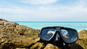 假期起动这里概念、佩戴水肺的潜水设备在白海石头与透明的海和天空在使用的背景中 免版税库存图片