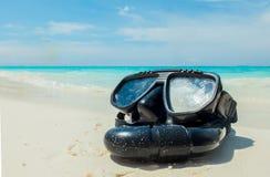 假期起动这里概念、佩戴水肺的潜水设备在白色海沙海滩与透明的海和天空在使用的背景中 图库摄影