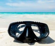 假期起动这里概念、佩戴水肺的潜水设备在白色海沙海滩与透明的海和天空在使用的背景中 库存图片