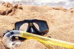 假期起动这里概念,在白色海沙海滩的佩戴水肺的潜水设备 免版税图库摄影
