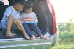 假期,旅行-家庭准备好旅行为暑假 手提箱和汽车有海的背景的 有地图的男孩在手中 库存图片