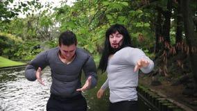 假肌肉服装的两帅哥在浮动小船命中树枝 股票视频