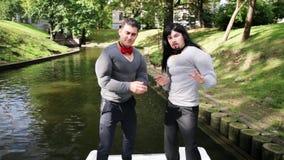 假肌肉的两个可爱的人在移动的小船填塞了服装站立并且拍手 股票视频