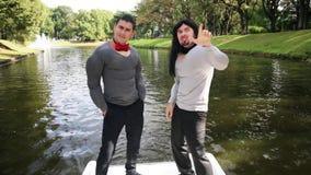 假肌肉的两个滑稽的人在移动的小船填塞了服装跳舞并且唱歌 股票录像