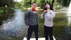 假肌肉的人填塞了服装紧蝶形领结和舞蹈在浮动小船 股票录像