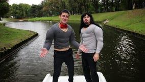 假肌肉胸口和胳膊的两个可爱的人在小船填塞了服装唱歌 影视素材