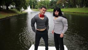 假肌肉胸口和胳膊的两个可爱的人在小船填塞了服装站立 股票录像