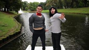 假肌肉胸口和胳膊的两年轻人在小船填塞了服装站立 股票视频