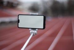 假装一个黑智能手机用selfie棍子 设计模板的白色屏幕在红色轨道的背景 免版税库存图片