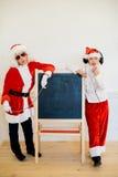 假装两个的男孩他是坏圣诞老人在黑人委员会附近 免版税库存照片