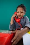 假装作为女实业家的女孩谈话在土地线电话 免版税库存照片