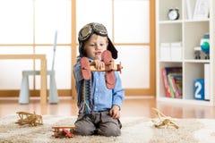假装儿童的男孩是飞行员 在家使用与玩具飞机的孩子 旅行和梦想概念 图库摄影