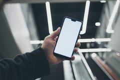 假装在手中一个智能手机,在一个自动扶梯的背景在一盏购物中心和光亮灯的 免版税库存图片
