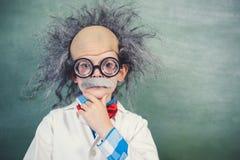 假装女小学生的画象是一位老师在教室 免版税图库摄影