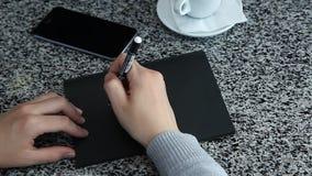 假装女性的手写在黑纸放置的桌 影视素材