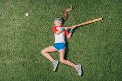 假装小女孩的顶视图打在草的棒球 库存图片