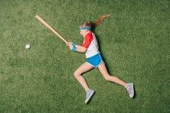 假装小女孩的顶视图打在草的棒球 免版税库存照片