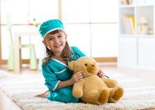 假装微笑的儿童的女孩她是一位医生在医院 免版税库存图片