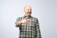 假装或坏笑话概念 指向手指和暴牙的微笑的成熟人 免版税库存图片