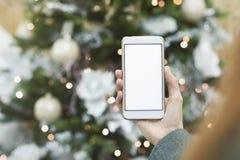假装智能手机在女孩的手上圣诞树的背景的与欢乐装饰的 库存图片
