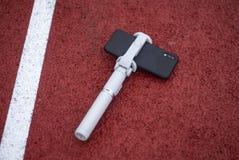 假装有一个三脚架的一个黑智能手机在红色轨道的背景跑和体育体育场的 库存照片