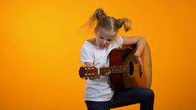 假装滑稽的青春期前的女孩弹作梦的吉他成为著名摇滚明星 股票录像