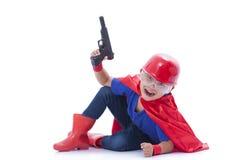 假装的孩子是有玩具枪的一个超级英雄 免版税库存图片