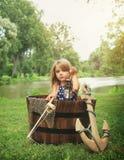 假装的孩子钓鱼在木小船由水 免版税图库摄影